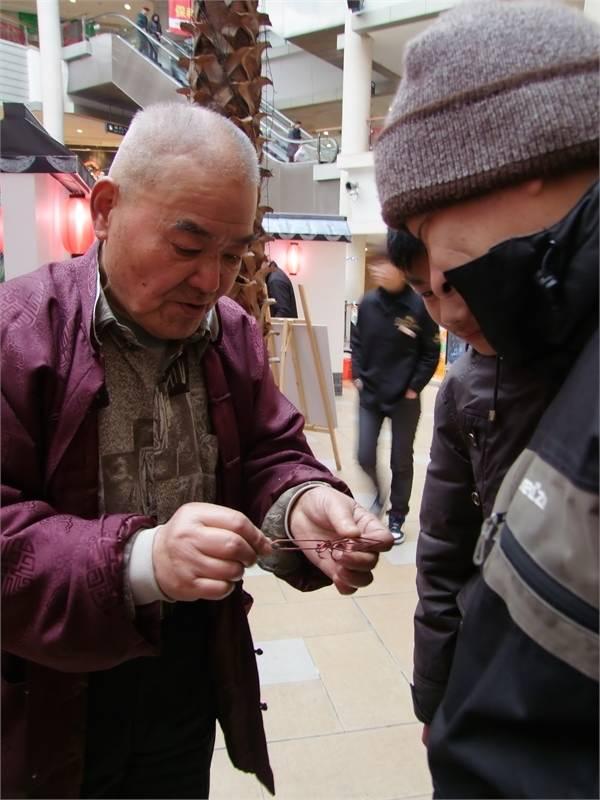Wire puzzle maker Ruan Genquan at the Asian Art Museum of San Francisco, 2000